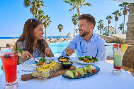 Young couple eating in a pool restaurant