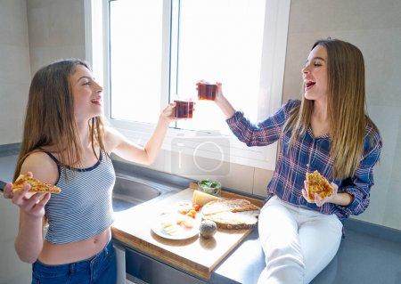 Photo pour Meilleur ami adolescent filles manger de la pizza dans la cuisine au déjeuner avoir du plaisir - image libre de droit