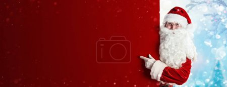 Photo for Santa Claus Holding Blank Advertisement Banner Red Background with Copy Space - Royalty Free Image
