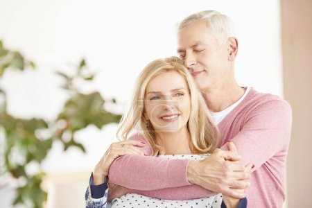 Photo for Shot of a happy senior couple standing together in living room. Smiling husband with closed eyes embracing his beautiful wife. - Royalty Free Image