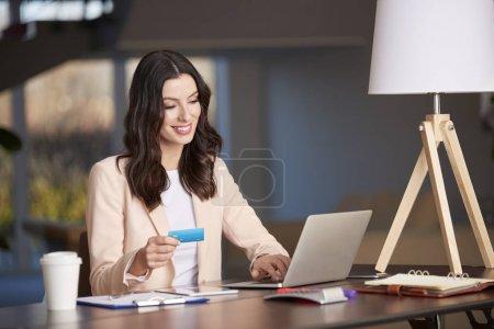 Photo pour Prise de vue d'une jeune femme d'affaires heureuse faisant ses opérations bancaires en ligne tout en travaillant au bureau . - image libre de droit