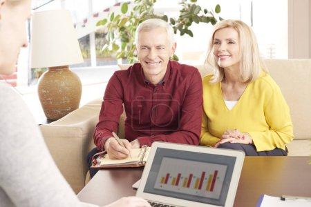 Photo pour Tir d'un vieux couple heureux assis à la maison et de consulter leur conseiller financier à l'épargne. - image libre de droit