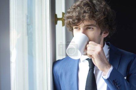Photo pour Gros plan d'un jeune homme d'affaires souriant avec une tasse de café en regardant par la fenêtre . - image libre de droit
