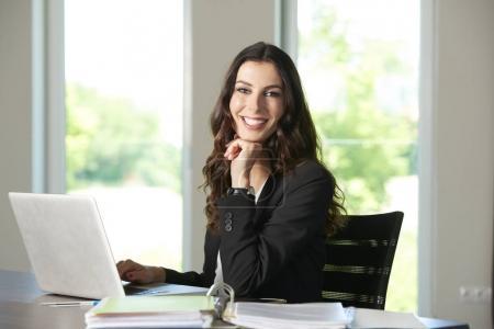 Photo pour Prise de vue d'une jeune femme d'affaires heureuse travaillant ordinateur portable dans le bureau . - image libre de droit