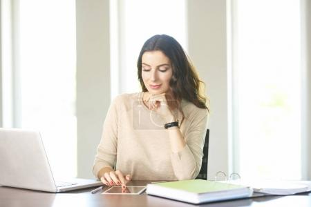 Photo pour Shot of a smiling businesswoman using digital tablet while sitting at office desk and working online. - image libre de droit