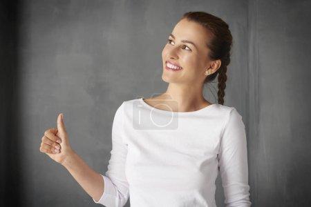 Photo pour Prise de vue d'une jeune femme qui a réussi à donner le pouce vers le haut tout en se tenant au mur gris . - image libre de droit