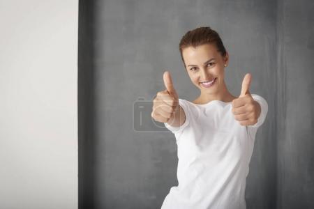Photo pour Prise de vue d'une jeune femme qui a réussi à donner les pouces vers le haut tout en se tenant au mur gris . - image libre de droit
