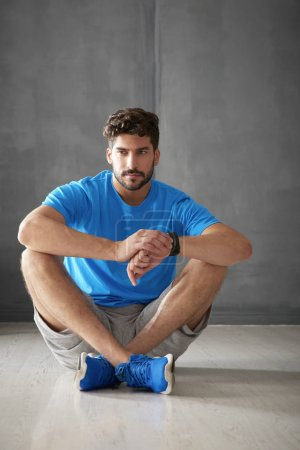 male personal trainer sitting in gym