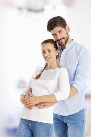 Photo pour Un jeune couple heureux debout dans le salon. bel homme étreignant sa belle petite amie par derrière . - image libre de droit