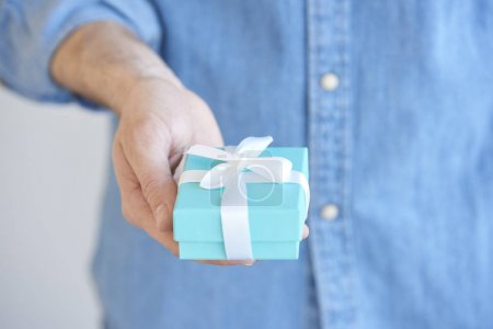Close-up of man holding a present box in his hand.
