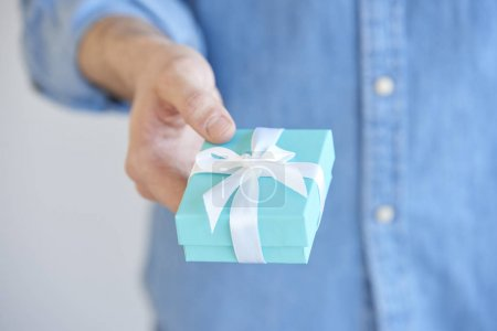Close-up of man holding a present box in his hand and give it.