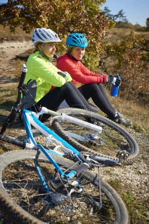 Full length shot of two female cyclist sitting on the rock and relaxing while out mountain biking.