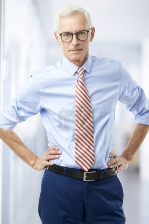 Confident senior man wearing shirt with rolled up sleeves while standing in the office.