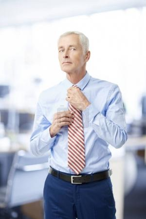 Senior businessman standing in the office while wearing shirt and knotting tie.