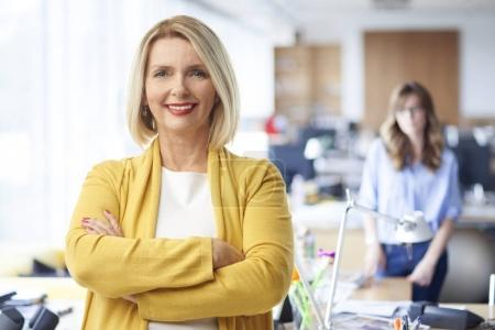 Photo for Beautiful mature sales businesswoman wearing casual clothes and smiling while standing with arms crossed at the office. - Royalty Free Image