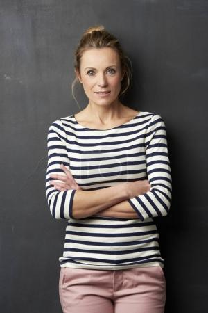 Confident mature woman looking at camera while standing at gray wall.