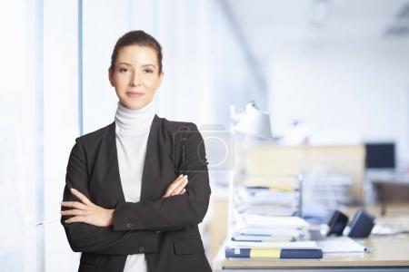 Photo pour Smiling executive financial advisor businesswoman standing with arms crossed at the office. - image libre de droit