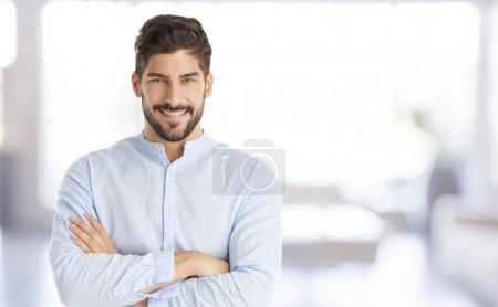 Portrait of a happy young man standing with arms crossed and looking at camera.