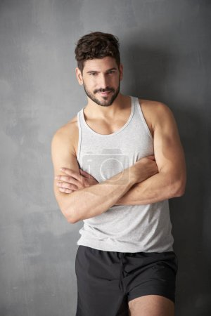 Three quarter length of young male personal trainer standing with crossed arms