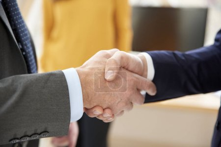 Photo pour Gros plan de deux hommes d'affaires en costume et serrant la main . - image libre de droit