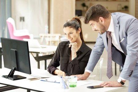 Photo pour Une conseillère financière séduisante, femme d'affaires assise au bureau tandis qu'un bel homme d'affaires comptable se tient à ses côtés pour la consulter au sujet de son plan d'affaires. Travail d'équipe dans le bureau. - image libre de droit