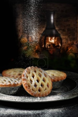 Photo for Festive Christmas mince pies with powdered sugar against a rustic background with generous accommodation for copy space. - Royalty Free Image