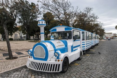 Close view of a long Tourist train in faro city parked on garden Manuel Bivar near the docks.