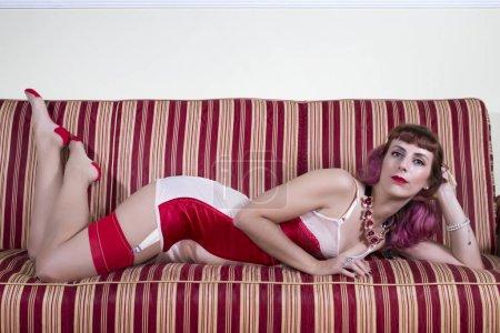 Photo pour Fille avec la lingerie de cru rouge avec un sofa rayé dans le salon. - image libre de droit