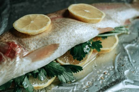 Photo for Fresh fish with parsley and lemon on foil prepared for baking - Royalty Free Image