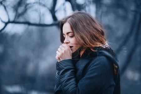 Photo pour Jolie jeune femme charmante dans un manteau sombre marchant dans le parc d'automne et réchauffe les mains gelées. Nuageux. Couleurs douces de la nature . - image libre de droit