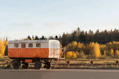 old white orange construction trailers on a background of autumn forest