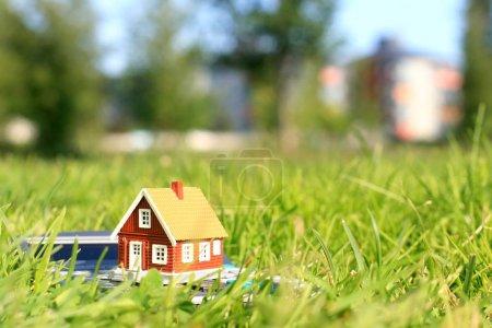 Photo pour Maison et calculatrice. L'immobilier sur le fond. - image libre de droit