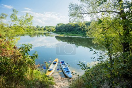 Inflatable boats on the pebbly Bank of the river. Kayaks in clear water