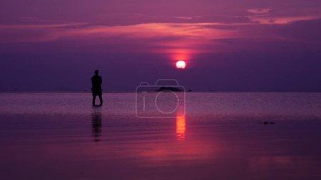 Photo pour Suivez vos rêves, silhouette d'homme debout dans la mer au coucher du soleil - image libre de droit