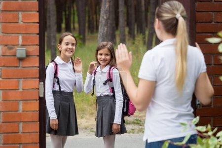 Photo pour Jeune mère de dire au revoir à ses filles d'aller à l'école - image libre de droit