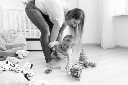 Photo for Black and white photo of young mother trying to calm down her crying baby boy - Royalty Free Image