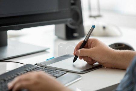 Photo pour Gros plan photo de graphiste mâle tenant stylet et dessin sur tablette graphique - image libre de droit