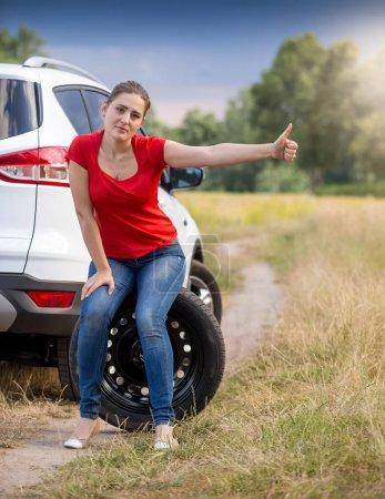 Photo pour Femme bouleversée avec voiture cassée tenant pouce vers le haut et auto-stop - image libre de droit