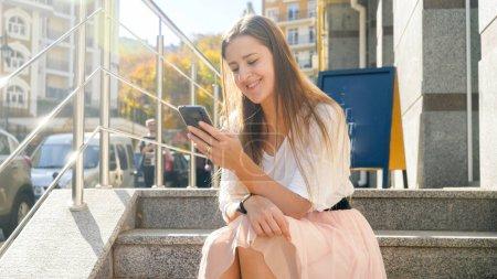 Photo pour Photo tonée d'une fille souriante et heureuse assise dans un escalier dans la rue et naviguant sur Internet sur un téléphone intelligent. - image libre de droit
