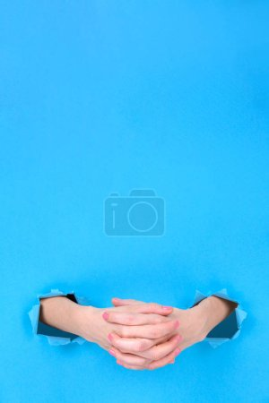 Photo for Girl hands close-up folded in a castle on a blue torn paper background. Hands symbolize the closeness, the experience. space for text on top - Royalty Free Image
