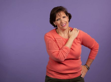 Middle Aged woman with shoulder pain holding her l...