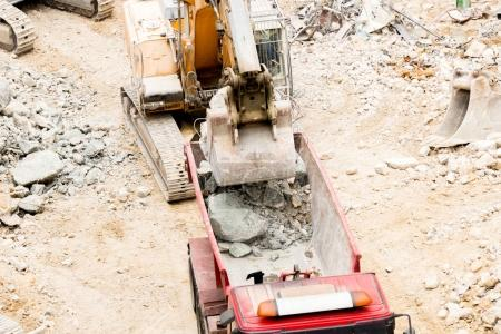 Excavator puts stones and debris into truck