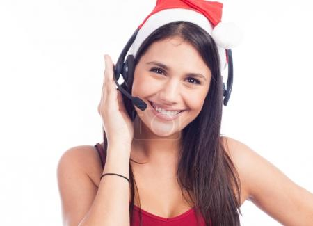 smiling woman with headset in santas hat