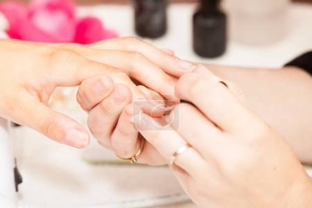 manicurist laying nail polish on hand