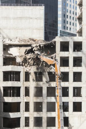 demolition of high concrete building with excavator