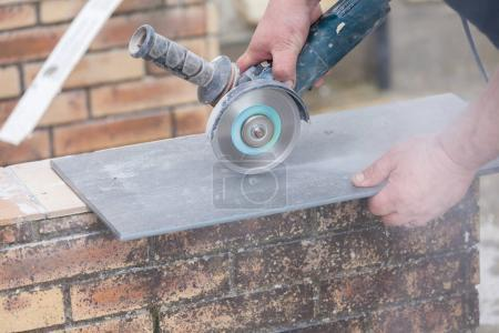 tiler cutting tile with a grinder at construction site
