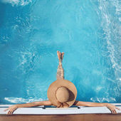 Top view of woman in straw hat relaxing in swimming pool at luxu