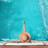 Back view of woman in straw hat relaxing in turquoise swimming p