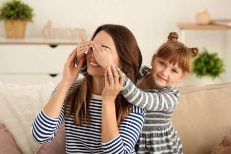 Foto de Feliz chica que cubre los ojos de su madre en casa - Imagen libre de derechos
