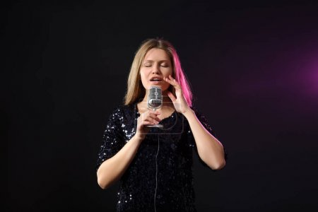 Photo for Beautiful young female singer with microphone on stage - Royalty Free Image